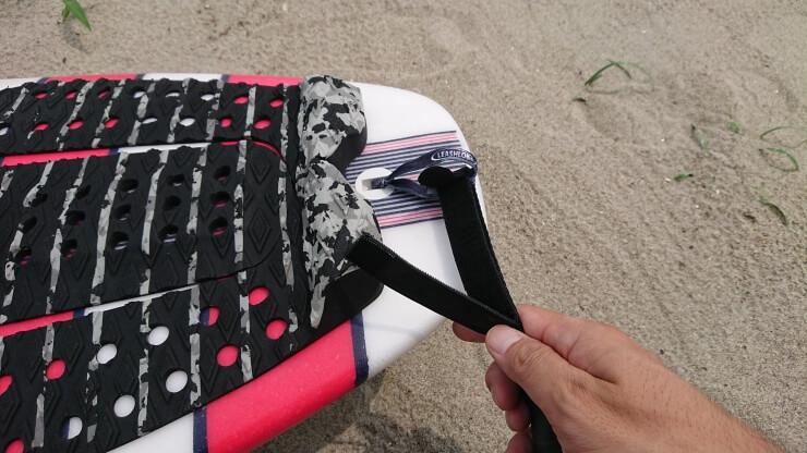 サーフィン用リーシュコードのレールセーバーが紐の先端に来るように留めている途中