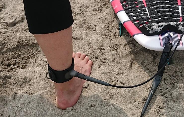 ウエットスーツをまくり上げた足にサーフィン用リーシュコードのアンクルカフを巻く